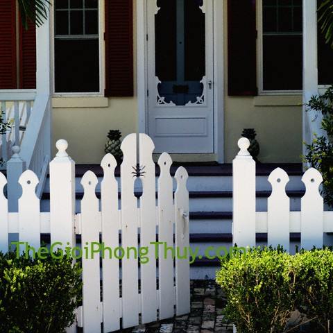 White picket fence in front of porch with red shutters on windows --- Image by © Dana Hoff/Beateworks/Corbis