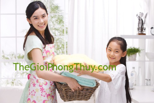 Mother and daughter holding basket of towel